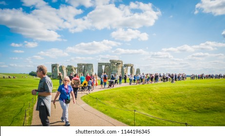 Salisbury, Wiltshire / UK - 08 25 2017: People, visitors walking on the road towards Stonehenge world heritage site in green countryside landscape. Summer holidays destination in the UK, Europe.