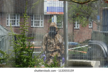 Salisbury, Wiltshire, UK. April 25 2018. Novichok decontamination worker in a mask standing in the area where Sergei and Yulia Skripal were found poisoned and unconscious in Salisbury England