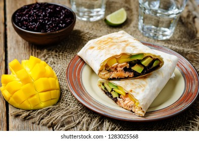 Salmon avocado mango black rice burritos on a wood background. toning. selective focus