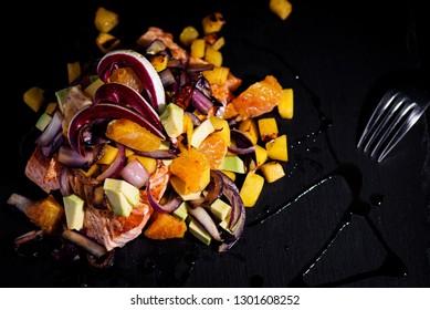 salmon with avocado mango radicchio and orange - black background