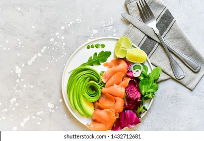 salmon and avocado salad with arugula and lime. on a white plate. healthy lunch. ketogenic diet  food (keto diet).