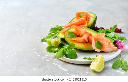 salmon and avocado salad with arugula and lime. on a white plate. healthy lunch. ketogenic diet  food (keto diet)