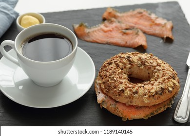 Salmon bagel sandwich and a cup of coffee on a slate cutting board
