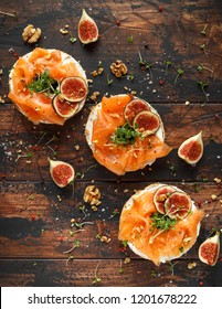 Salmon Bagel Sandwich with figs, cress salad, walnuts, cream cheese and grain on rustic wooden background. healthy breakfast