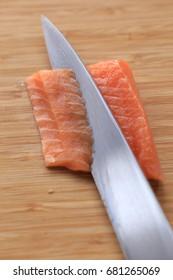 salmon being sliced for nigiri sushi