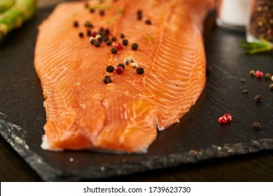 Salmon with black pepper on plate close up.