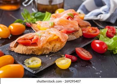 salmon bruschetta with cherry tomato and chili pepper