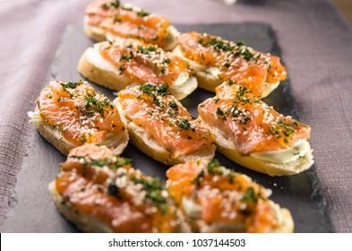 Salmon bruschettas set on a dark tile