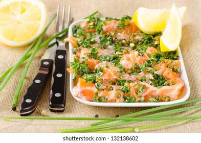 Salmon carpaccio - fresh salmon slices in marinade on burlapsack