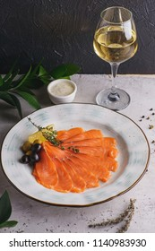 Salmon carpaccio with olives and lemon on gray stone table and black background with greens and ingredients and glass of white wine. Appetizer and snack.