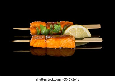 Salmon cooking on a grill. On a black background with reflection