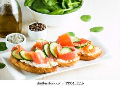 Salmon, cucumber and cream cheese bruschetta. Italian tapas, antipasti with vegetables, herbs and oil on grilled ciabatta and baguette bread. Sandwich.
