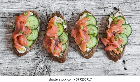 Salmon, cucumber and cream cheese rye sandwich on the wooden background, top view. Delicious snack or appetizer for wine.