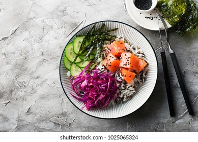 Salmon cucumber wild rice red cabbage leaves nori pokebowl. Top View. Poke bowl trend