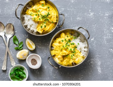 Salmon curry and rice in curry dishes on grey background, top view. Indian cusine style. Flat lay