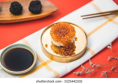 Salmon eggs or Ikura in Japanese style sushi fresh from raw salmond fish in studio lighting with red background. Sushi set menu - image