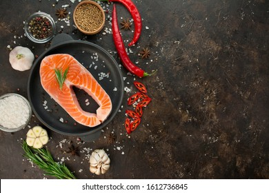 Salmon fillet with aromatic herbs, spices and vegetables on a dark background. Cooking concept. Culinary background. Food background. Healthy food balance. Table background menu. Copy space.