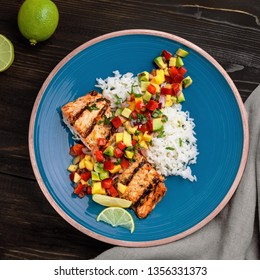 Salmon fillet cooked on grill with exotic sauce made of mango, avocado and pepper on blue plate. Delicious fish meal with jasmine rice. Top view shot above.