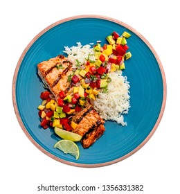 Salmon fillet cooked on grill with exotic sauce made of mango, avocado and pepper on blue plate. Studio shot above isolated on white background. Top view.