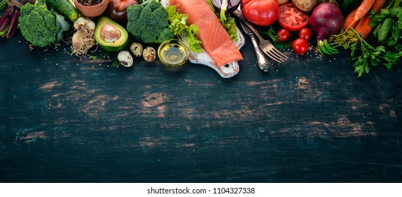Salmon fillet and fresh vegetables. Healthy food. On a black wooden background. Healthy food. Top view. Copy space.