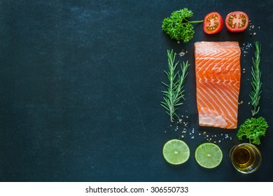 Salmon fillet with garnish on blackboard
