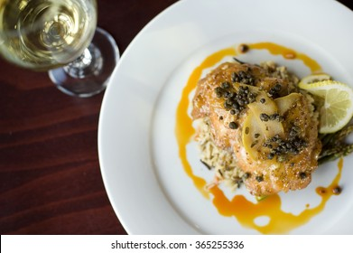 Salmon fillet with lemon and capers in a pear reduction sauce over asparagus and wild rice, paired with white wine.