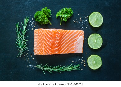 Salmon fillet with lemon rosemary parsley and garnish  on blackboard