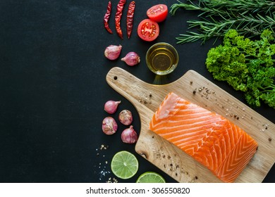Salmon fillet with lemon rosemary parsley and garnish  on wooden board