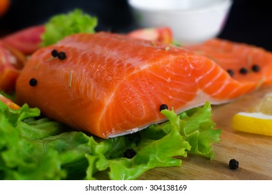 Salmon fillet with lettuce and black pepper ready to cook