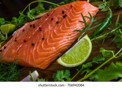Salmon fillet with lime slice, spices and greens on a wooden background. Dinner cooking ingredints.