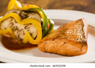 Salmon fillet with mixed vegetables on wooden background.