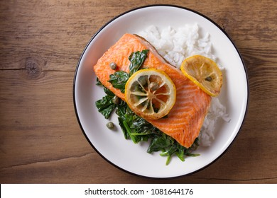 Salmon fillet with rice, spinach and lemon. Salmon with garnish. Fish for healthy dinner. View from above, top