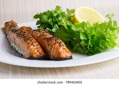 Salmon Fillet With Salad And Lemon On A Plate