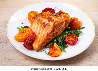 Salmon fillet with spinach, tomatoes and herbs, horizontal