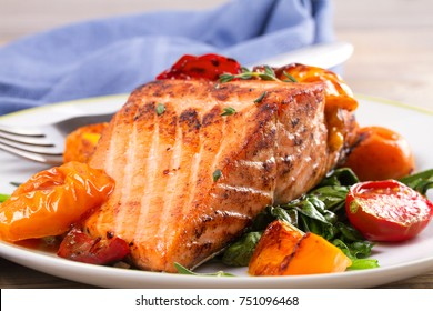 Salmon fillet with spinach and tomatoes on white plate on rustic wooden background