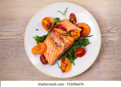 Salmon fillet with spinach and tomatoes on white plate on rustic wooden background. Overhead, top view