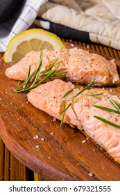 Salmon fillets. Grilled salmon, rosemary - herb decoration on vintage pan or wooden board. roasted fish , wooden table. Studio shot.