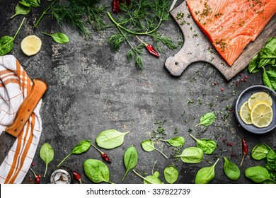 Salmon fish fillets on cutting board and fresh ingredients for cooking on rustic background, top view frame. Healthy or diet food concept.