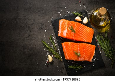 Salmon fish with ingredients at black table.