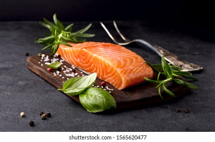 Salmon fish on the stone with fresh basil, rosemary and spices.  Steak on black background.