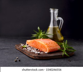 Salmon fish on the stone with rosemary and salt. Fish with spices.