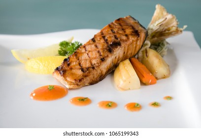 Salmon fish seafood grilled steak on plate in restaurant ready to serve
