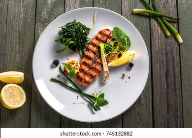 Salmon fish stake cooked on a grill with healthy salad on a plate. Healthy food made of fish and vegetables on a table. Top view.