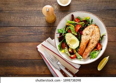 Lachs-Fisch Steak gegrillt, Avocado und frischer Gemüsesalat mit Tomate, Glockenpfeffer und Gemüse. Draufsicht