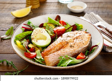Salmon fish steak grilled, avocado and fresh vegetable salad with tomato, bell pepper and leafy vegetables