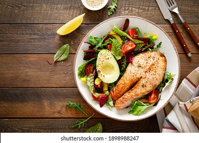 Salmon fish steak grilled, avocado and fresh vegetable salad with tomato, bell pepper and leafy vegetables. Top view, copy space.