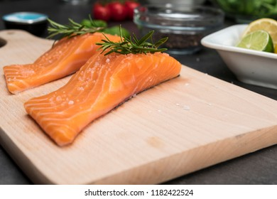 Salmon fish steaks on wooden cutting board. Closeup on food ingredients.