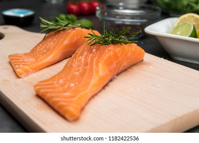 Salmon fish steaks with rosemary on wooden cutting board ready for cooking. Closeup on food ingredients.