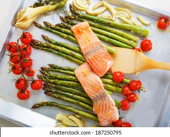 Salmon fish and vegetables: green aspargus, cherry tomatoes and fennel, on oven tray