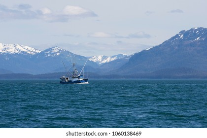 Salmon fishing boat in Lynn Canal in Southeast Alaska with mountains in the background.